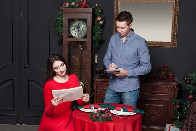 젊은 여성이 고급 레스토랑에서 메뉴를 탐색하고 웨이터가 주문을받습니다.