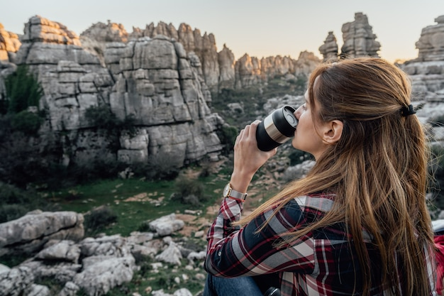 Young woman explorer drinking coffee from a thermos flask with the mountains in the background. concept of adventure, excursion and trips.