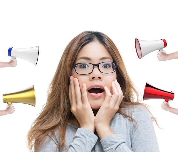 若い女性は白い背景の上のメガホンで驚きの顔を表現します。