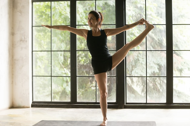 Young woman in extended hand to big toe pose