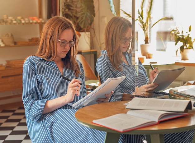 Young woman in eyeglasses in modern cafe with books and notebooks learning and preparing for exam