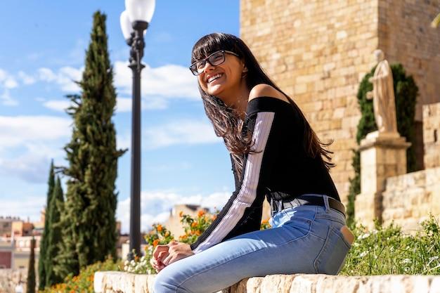 젊은 여자 안경 초상화, 돌로 벤치에 앉아 행복 미소, 카메라를 찾고