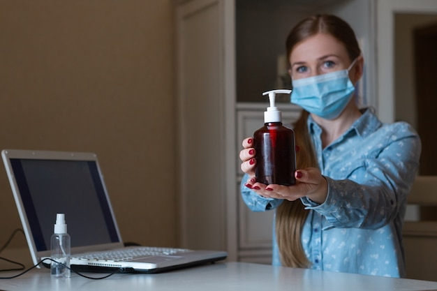Young woman in face mask disinfecting gadgets surfaces on her workplace