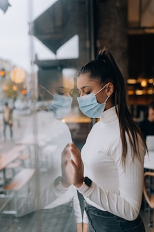 Young woman in face mask standing in front of windows in cafe