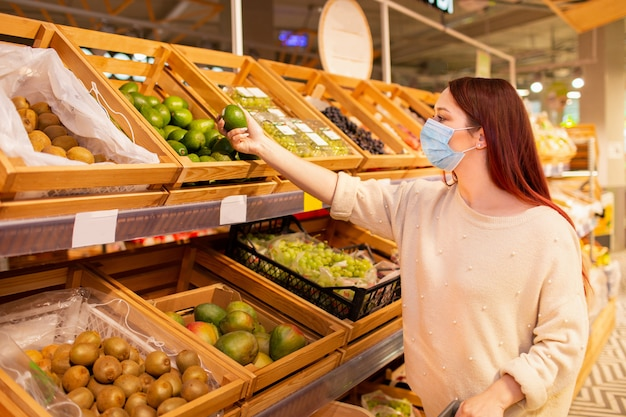 Young woman in face protective medical mask for protection from virus disease buying vegetables at grocery store or supermarket.