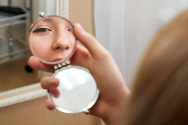 若い女性は小さな鏡で反射に直面します