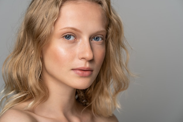 Young woman face with blue eyes, curly natural blonde hair and eyebrows
