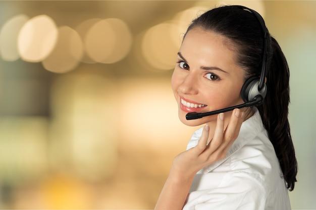 ヘッドフォン、コールセンター、またはサポートの概念を持つ若い女性の顔