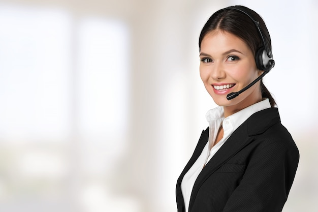 Young woman face with headphones, call center or support concept