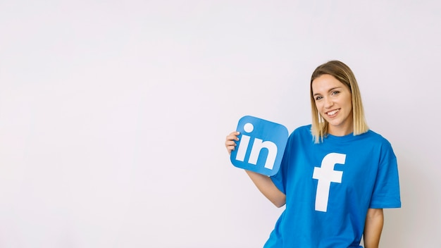 Young woman in facebook t-shirt holding linkedin icon