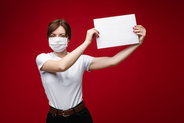 Young woman in facial mask for protection from virus epidemic holding paper