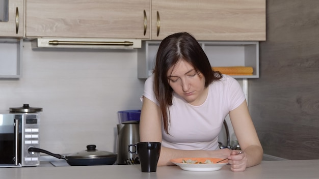 若い女性、眠りに落ちて、台所のテーブルで食事をします。