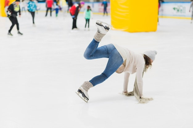 Young woman falling on skating rink