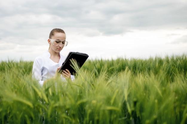 Молодая женщина-фермер в белом халате проверяет прогресс урожая на планшете на зеленом пшеничном поле. выращивается новый урожай пшеницы. концепция сельского хозяйства и фермы.