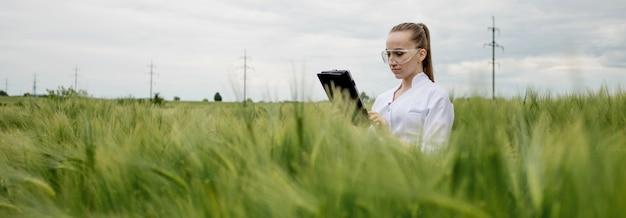 Молодая женщина-фермер в белом халате проверяет прогресс урожая на планшете на зеленом пшеничном поле.