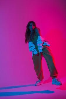 트렌디한 운동화를 신고 세련된 운동복을 입은 젊은 여성 패션 모델이 다양한 색상의 현대적인 스튜디오에서 춤을 추고 있습니다. 매력적인 소녀 댄서는 네온 핑크 빛으로 스튜디오에서 춤을 즐깁니다.