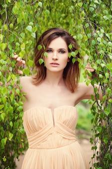 Фотомодель молодой женщины на предпосылке зеленой листвы.