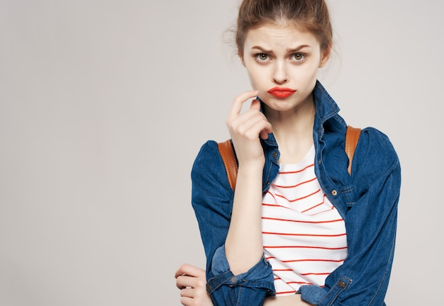 Young woman in fashionable clothes fun backpack school