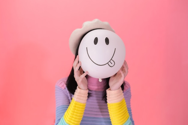 Young woman in fashionable style holding a positive emotion of balloon