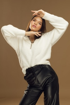 Young woman fashionably posing in studio, girl model brunette on a beige background in leather pants. high quality photo