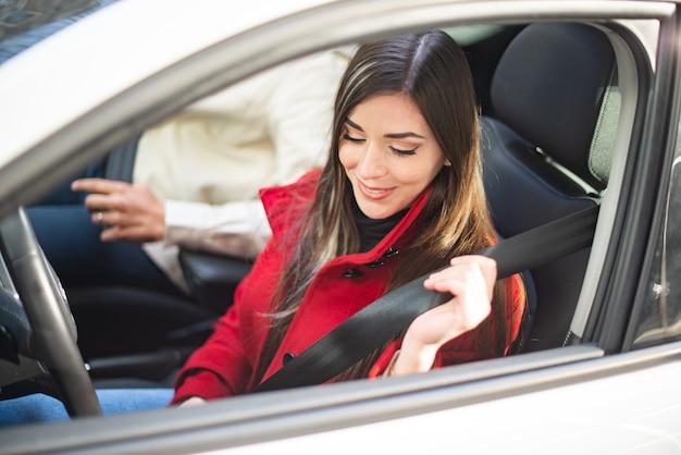그녀의 차에 안전 벨트를 고정 하는 젊은 여자