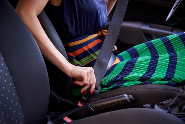 Молодая женщина пристегивает ремень безопасности в автомобиле.