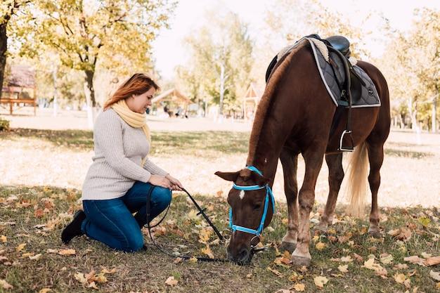 Молодая женщина кормит коричневую лошадь в осеннем парке