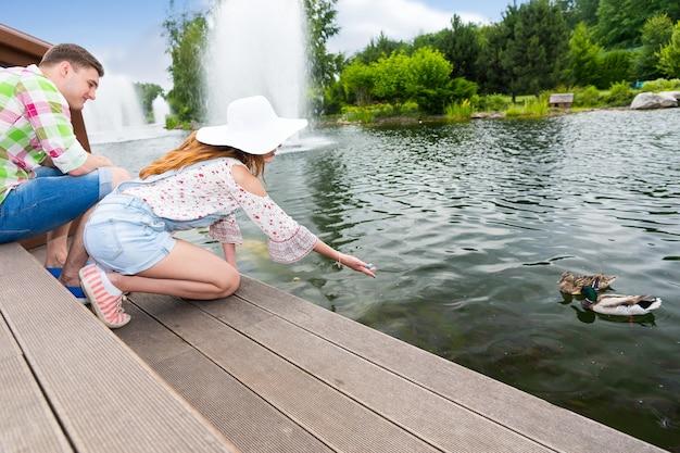 남자 친구가 나무 데크에 무릎을 꿇고 음식을 제공하는 연못에서 오리에게 먹이를 주는 젊은 여성