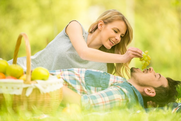 Young woman feeding her man with grape.