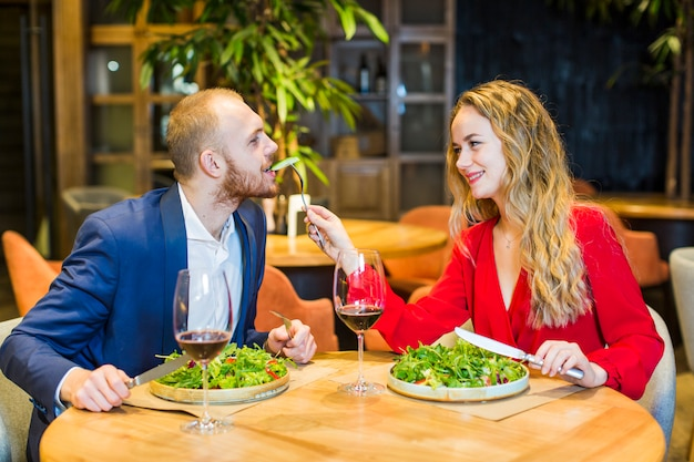 Young woman feeding man with salad in restaurant