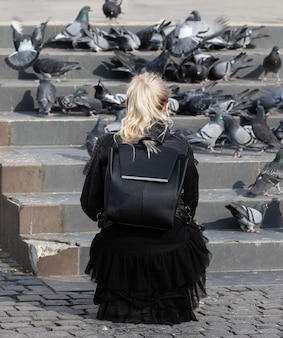 Молодая женщина кормит голубей на площади в центре города ужгород, украина