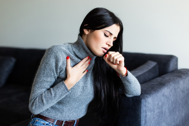 Young woman feel sick cought on couch at home