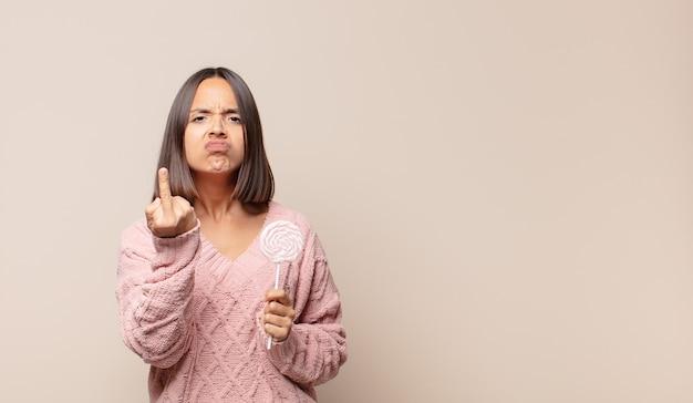 Молодая женщина чувствует себя злой, раздраженной, мятежной и агрессивной, переворачивает средний палец, сопротивляется