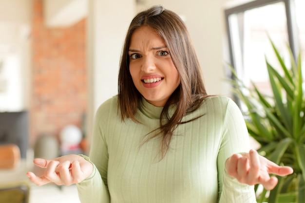 Молодая женщина чувствует себя невежественной и сбитой с толку, не уверенная, какой выбор или вариант выбрать, задаваясь вопросом