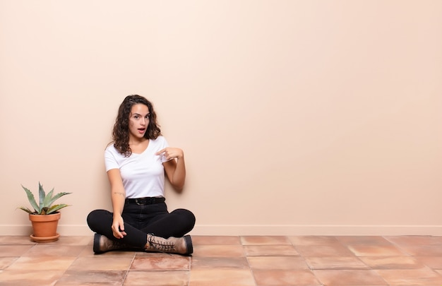 Young woman feeling confused, puzzled and insecure, pointing to self wondering and asking who, me? sitting a terrace floor