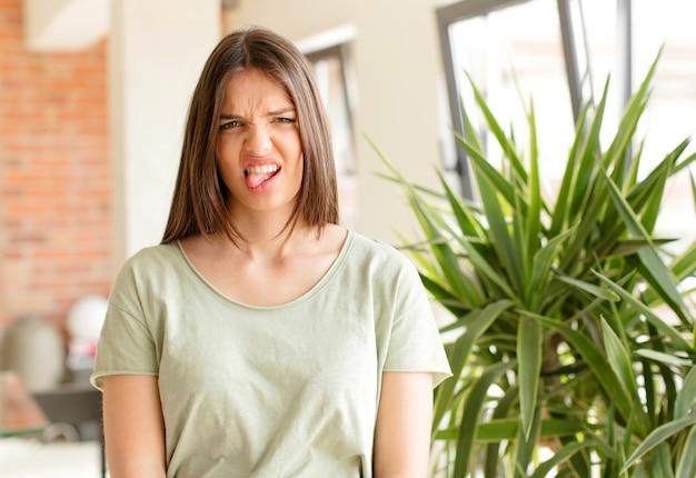 Молодая женщина чувствует отвращение и раздражение, высунув язык, не любя что-то противное и противное