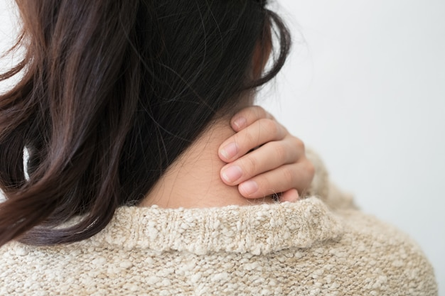 Молодая женщина чувствуя вымотанный и страдающий от боли в шее, концепции здоровья.