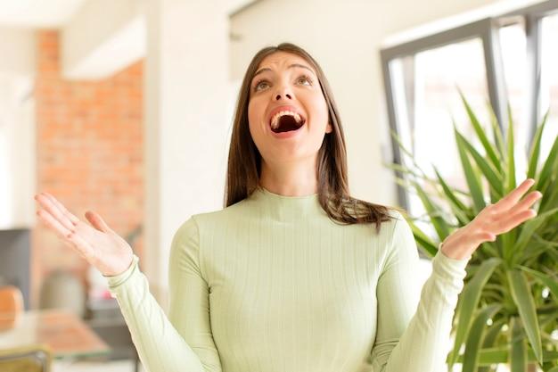 幸せを感じている若い女性は、空中に両手を上げて勝利を祝って幸運と驚きを驚かせました