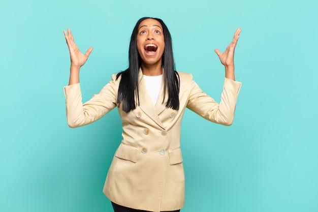 幸せ、驚き、幸運、驚きを感じ、両手を空に上げて勝利を祝う若い女性