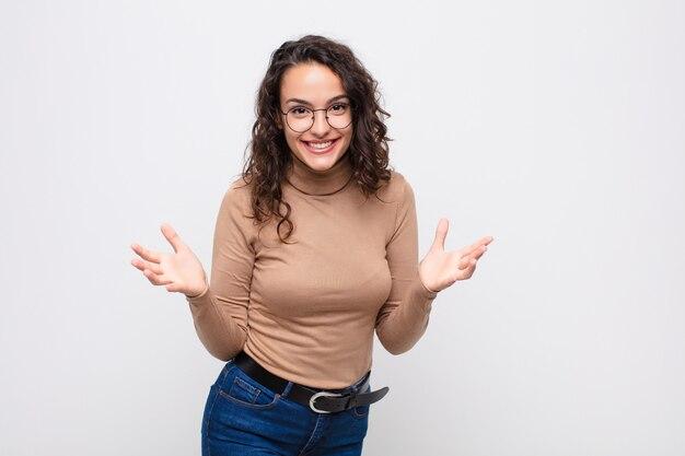 Молодая женщина чувствует себя счастливой, удивленной, удачливой и удивленной, как будто серьезно говорит: «боже»? невероятно на белой стене