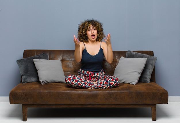 Молодая женщина чувствует себя счастливой, удивленной, удачливой и удивленной, как будто серьезно говорит: «боже»? невероятно сидеть на диване.