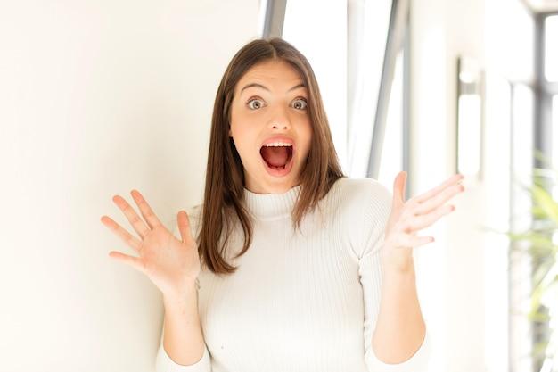 행복을 느끼는 젊은 여자는 놀라거나 충격을 받고 웃고 믿을 수없는 것에 놀랐습니다.