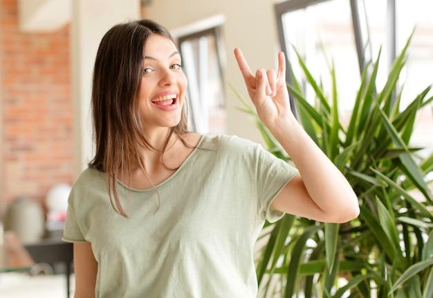 幸せな楽しみを感じている若い女性自信を持って前向きで反抗的な手で岩や重金属の看板を作る