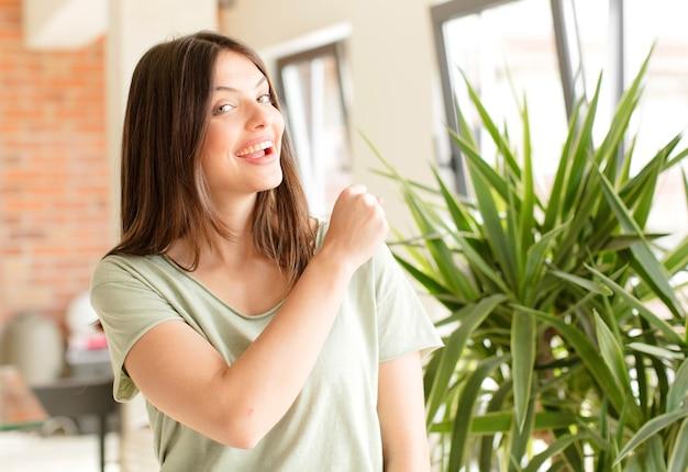 Молодая женщина чувствует себя счастливой, позитивной и мотивированной к успеху, когда сталкивается с проблемой или празднует хорошие результаты