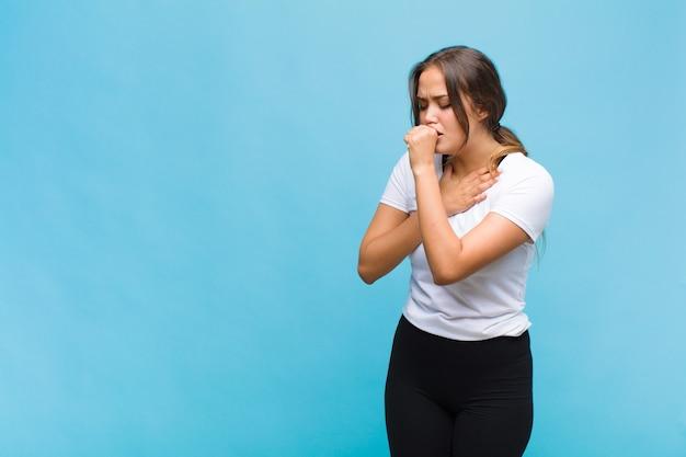 Молодая женщина чувствует себя плохо с симптомами гриппа и боли в горле, кашляет с прикрытым ртом
