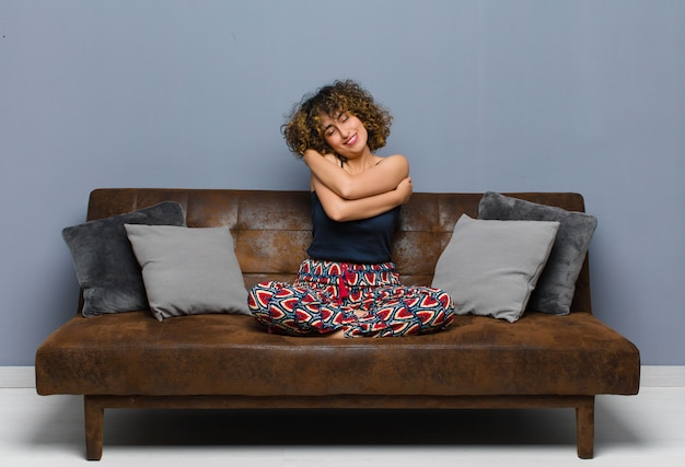 Young woman feeling in love, smiling, cuddling and hugging self, staying single, being selfish and egocentric sitting on a sofa.