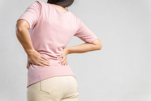 Молодая женщина, чувствуя боль в спине на белом. здравоохранение и медицинская концепция.