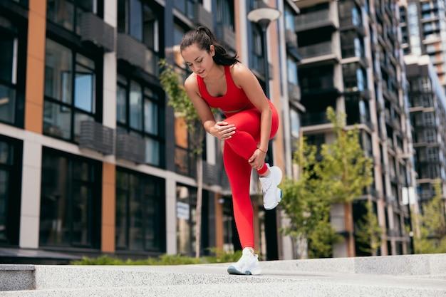 屋外でのスポーツトレーニング中に足に痛みを感じる若い女性。赤いスポーツウェアと白いスニーカーの女の子が片足で立っていて、左足にけいれんを感じています。