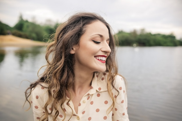 Young woman feeling relaxed near lake