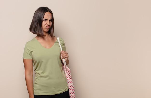 젊은 여성이 슬프거나 화를 내거나 분노를 느끼고 부정적인 태도로 측면을 바라보고 불일치에 눈살을 찌푸립니다.
